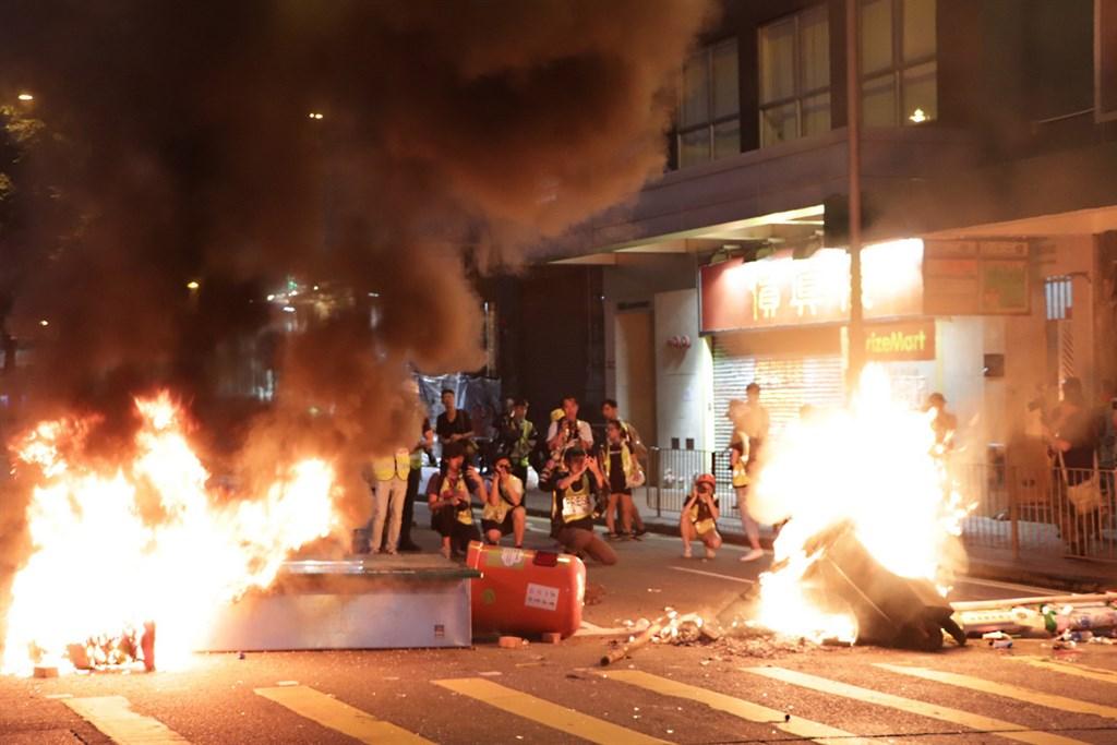 香港警察隊員佐級協會發聲明譴責反送中14日與15日遊行,批評示威者違法暴力與破壞,圖為15日面對港警強力清場,示威者沿途焚燒雜物。(中央社檔案照片)