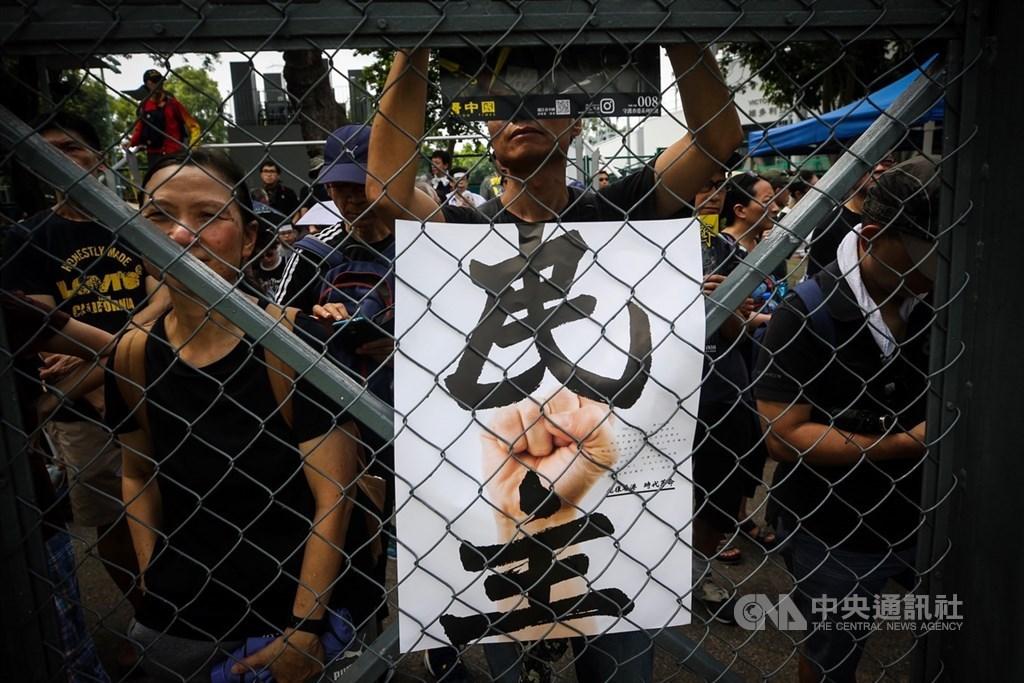 印度中國專家謝鋼撰文指出,中國在香港加強「一國」而非「兩制」引發香港人強烈反對。圖為8月11日維園反送中集會,民眾手持印有「民主」的標語表達訴求。(中央社檔案照片)