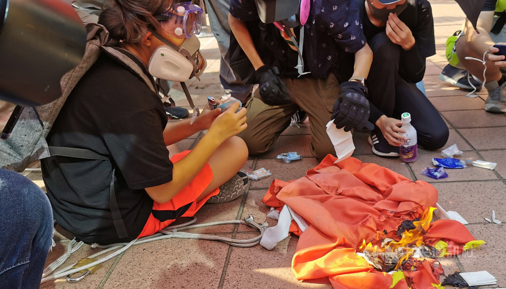 香港反送中人士21日下午舉行遊行,其中有人在屯門大會堂旁拉下中國國旗並燒燬。中央社記者張謙香港攝 108年9月21日