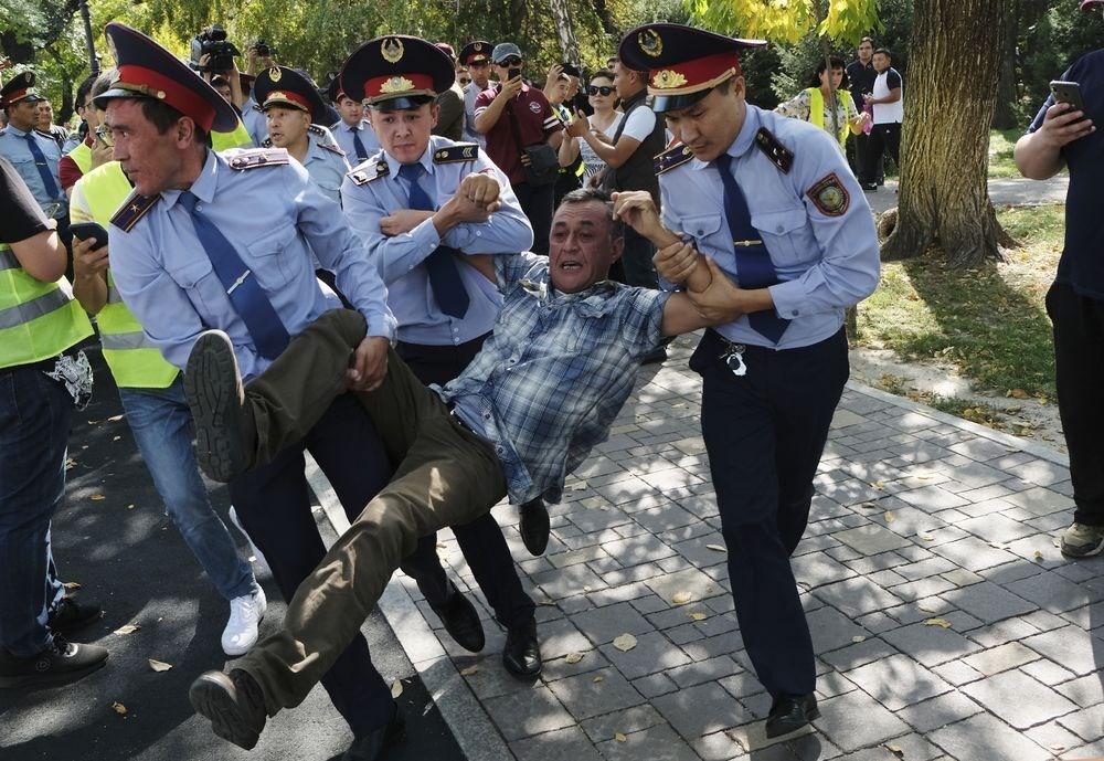 中國西北方的鄰國哈薩克最大城阿拉木圖21日爆發街頭示威,反對中國對哈薩克影響力日增是訴求之一,有示威者被警方強行拖上警車。(美聯社)