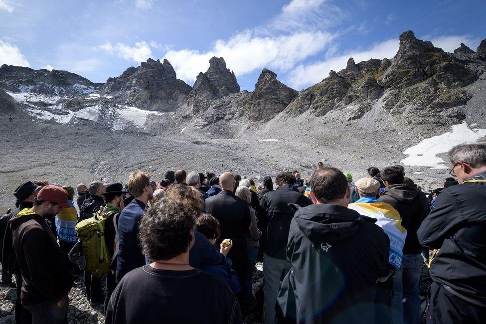 約100名瑞士居民22日穿黑衣爬上海拔近3000公尺的皮措爾山,緬懷逝去的冰川。(法新社提供)
