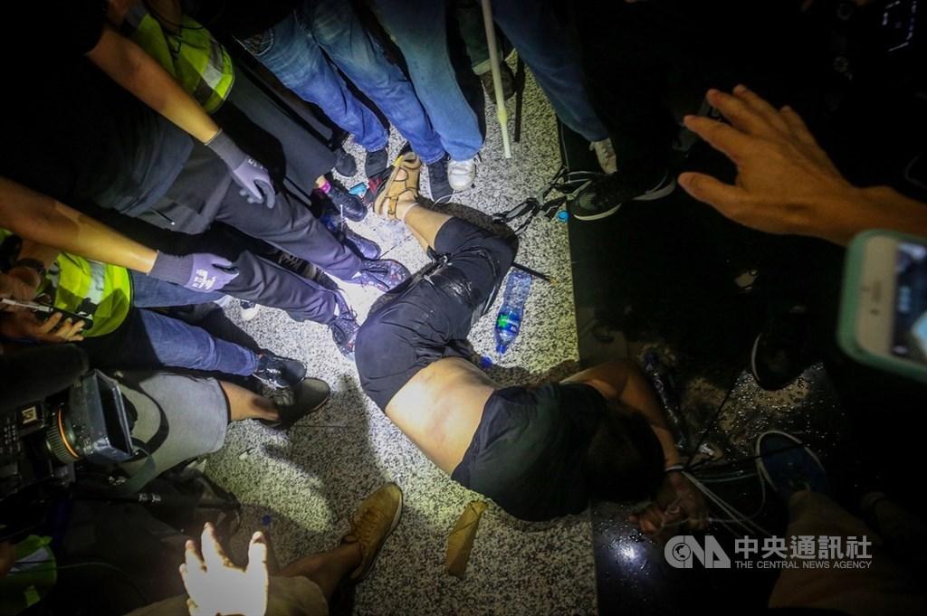 在香港「反送中」運動期間被群眾綑綁推打的環時記者付國豪(倒地者)在事件後名利雙收,除了在大陸聲名大噪,環時22日表彰表現突出者時,付國豪獲得人民幣10萬元的最高獎。(中央社檔案照片)