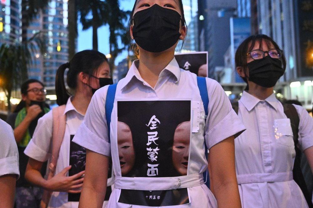 香港5日起實施「禁蒙面法」,香港教育局日前向全港學校發信,要求校方8日上午11時前回報戴口罩學生人數等。圖為香港示威者戴口罩抗議「禁蒙面法」。(檔案照片/法新社提供)