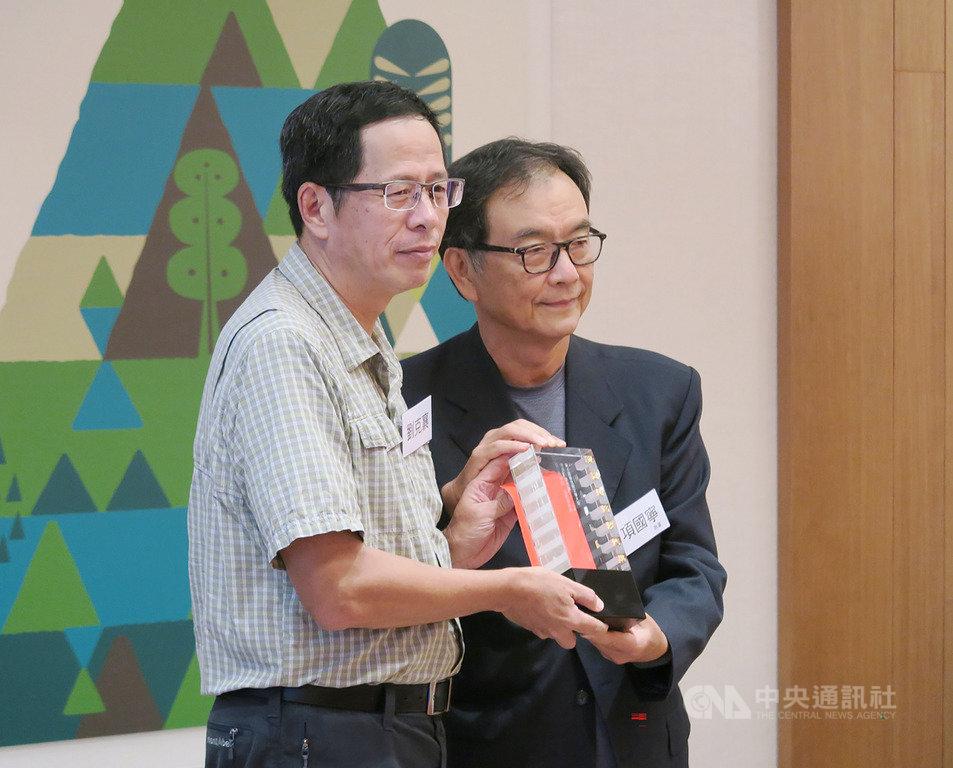 2019第6屆聯合報文學大獎贈獎典禮6日在台北舉行,本屆獲獎作家劉克襄(左)親自出席,從聯合報執行董事項國寧(右)手中接下獎座。劉克襄說,獲獎是提示他不要迷路,要重新再與這片土地對話。中央社記者陳政偉攝 108年10月6日