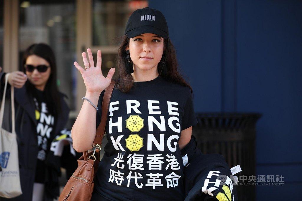 美國國會授權成立的「共產主義受害者紀念基金會」人員身穿挺香港T恤,在華府市區體育館外比出手勢,象徵香港反送中運動的「五大訴求,缺一不可」。中央社記者徐薇婷華盛頓攝 108年10月10日