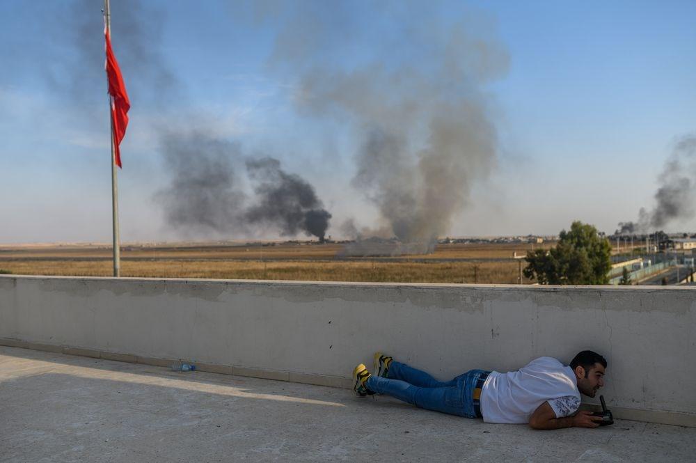 土耳其對庫德族發動軍事攻擊的第2天,1枚迫擊砲在土耳其阿克恰卡萊鎮(鄰敘利亞邊界)附近降落,記者趴下掩護自身安全。(法新社提供)