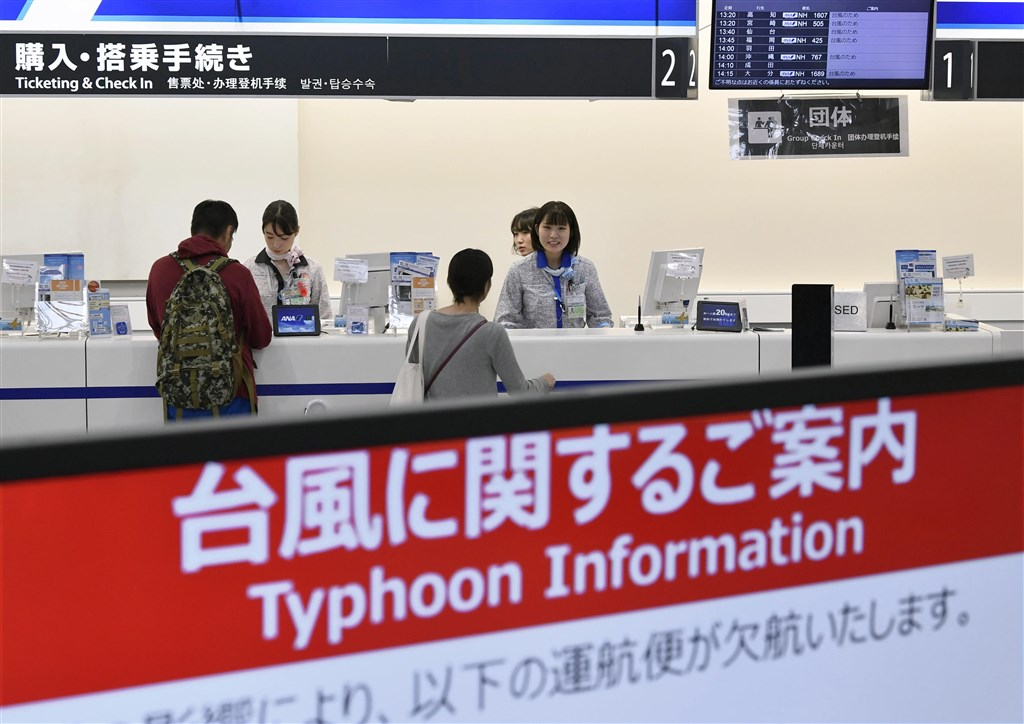 颱風哈吉貝襲日本,許多航班取消,大阪機場的航空公司人員向旅客說明。(共同社提供)