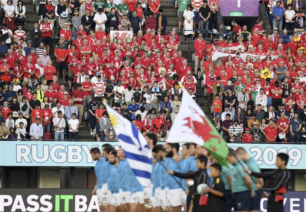 世界盃橄欖球賽分組賽事最後一天賽程13日在日本舉行,威爾斯與烏拉圭兩隊隊員在賽前與全場觀眾為颱風哈吉貝風災的罹難者默哀。(共同社提供)
