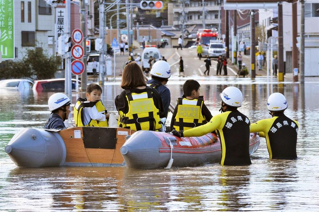 颱風哈吉貝侵襲日本部分地區,救難人員協助救出因淹水受困的民眾。(共同社提供)