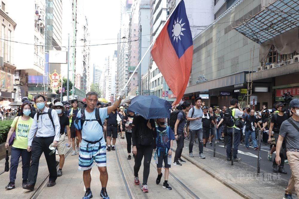 香港反送中示威仍持續進行,蘋果公司港版iPhone鍵盤隱藏中華民國國國旗表情符號。圖為1日反送中遊行,有人舉起中華民國國旗。(中央社檔案照片)