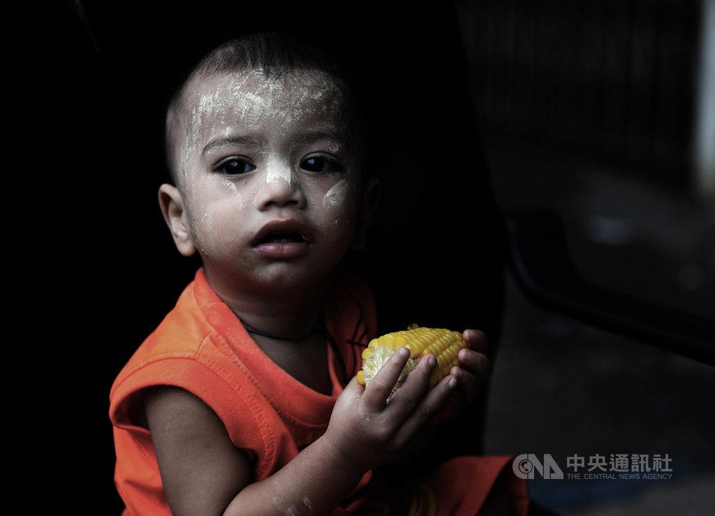 流落到馬來西亞難民外出拚經濟之際,兒童多半在住家附近巷弄玩耍,圖為稚齡幼童於傍晚昏暗光線下啃著熱呼呼玉米,天真無邪表情中似未感受成人生活壓力。中央社記者黃自強吉隆坡攝 108年10月18日