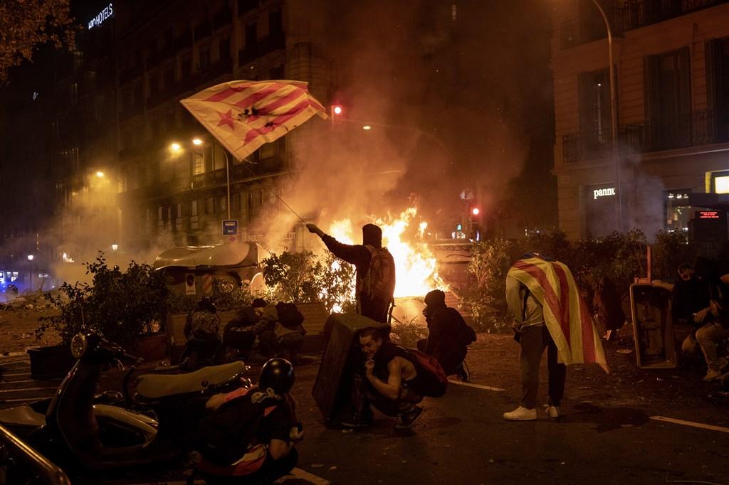 加泰隆尼亞挺獨活動到18日掀起一波高峰,且越夜越趨暴力,街頭出現火光、煙霧和石塊。(美聯社)