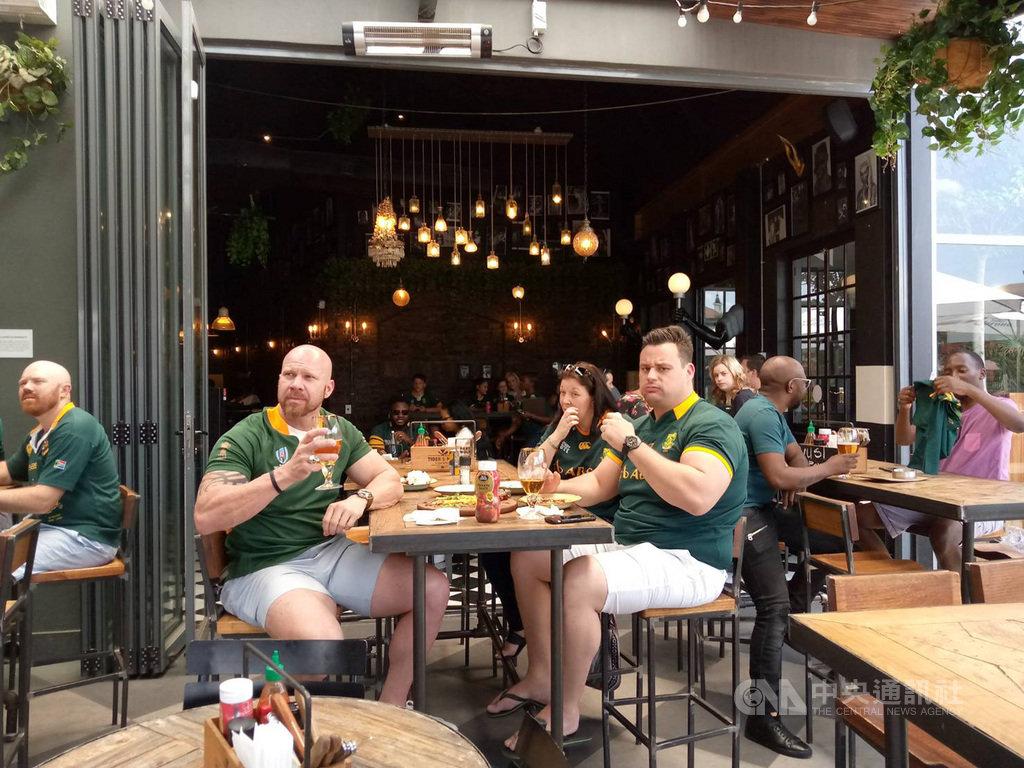 正在日本舉行的世界盃橄欖球賽,8強賽中最受矚目的是曾獲兩屆世界盃冠軍的南非隊與日本隊20日的比賽,結果南非擊敗日本晉級4強賽。圖為南非民眾身穿球隊制服齊聚餐廳一起為球隊加油。中央社記者徐梅玉約翰尼斯堡攝 108年10月20日