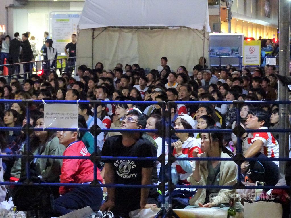 正在日本舉行的世界盃橄欖球賽,20日晚間日本隊在東京都調布市的球場出戰南非隊,這是日本球隊首度晉級8強賽,多處戶外設觀賽大螢幕,大批球迷湧至。圖為調布車站球迷加油區。中央社記者楊明珠東京攝 108年10月20日