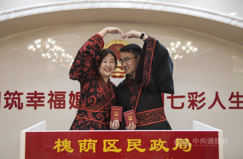 中國人大21日表示,對法定婚齡暫不做修改,消息傳出後,獲得多數未婚網友叫好,並指問題在晚不在早,他們沒錢結婚買房生小孩。圖為3月8日,山東濟南一對新人穿漢服前往民政局領結婚證。(中新社提供)中央社 108年10月22日