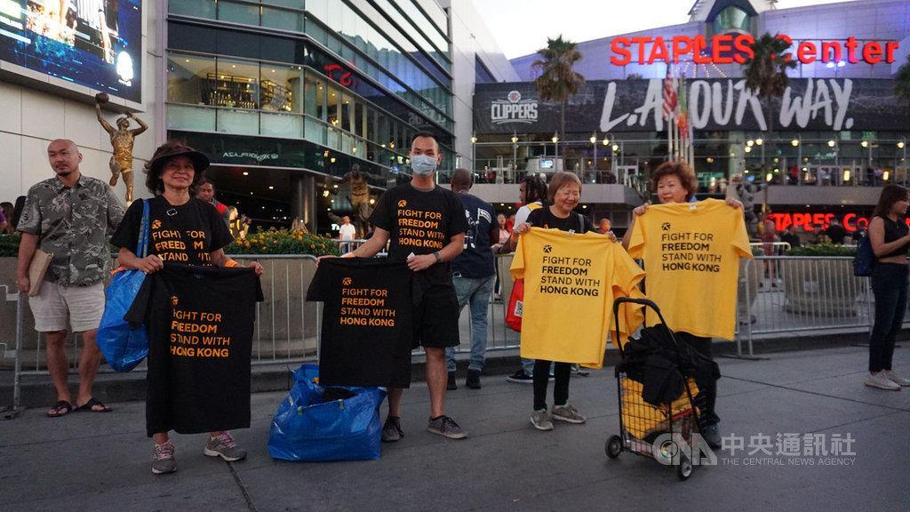 美國職籃NBA球季開打,22晚間在洛杉磯上演湖人對上快艇的開幕戰,場外有球迷號召支持香港、言論自由的活動,發放黑色、黃色上衣給進場球迷。中央社記者林宏翰洛杉磯攝 108年10月23日