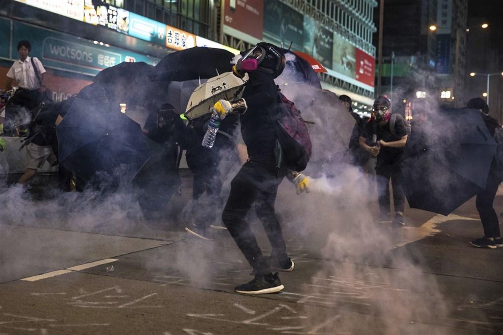 香港「反送中」網友27日下午發起追究警察暴力集會遭警方強力驅散後,晚間警民雙方集中在旺角彌敦道攻防,防暴警察多次推進驅散並發射多枚催淚彈。(法新社提供)