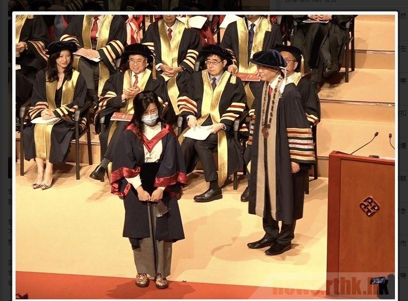 香港理工大學27日舉辦第25屆畢業典禮,有畢業生疑似為聲援「反送中」運動,戴口罩上台,校長滕錦光(前右)當場拒絕與畢業生握手合照。(圖取自香港電台網頁rthk.hk)