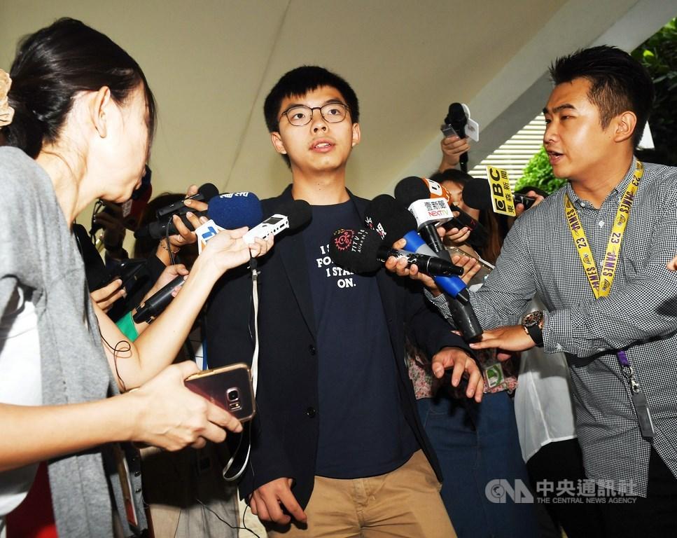 黃之鋒(中)26日晚間重申,「民主自決並非獨立,香港眾志亦無意改為主張香港獨立」。(中央社檔案照片)