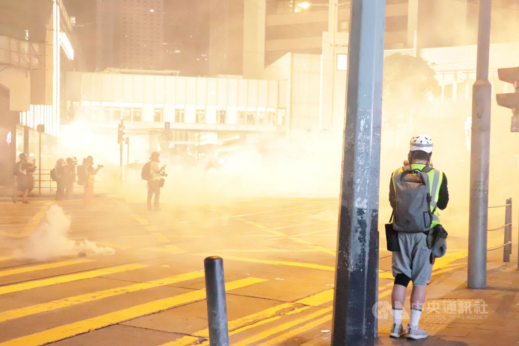 香港「反送中」網友趁著31日萬聖節之際發起集會遊行,許多人不顧禁蒙面法,戴著面具上街。圖為警方晚間10時左右在蘭桂坊附近發射催淚彈驅散示威者。中央社記者張謙香港攝 108年10月31日