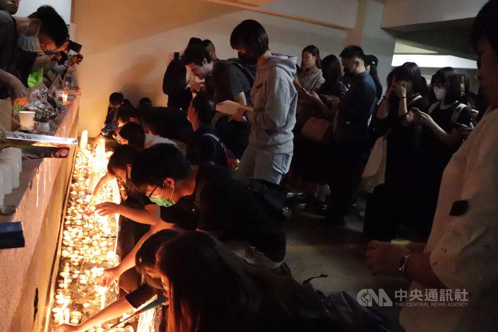 香港科技大學學生周梓樂日前墜樓後不治身亡。大批學生和市民8日晚間在事發地將軍澳尚德村停車場設立臨時靈台供人悼念、獻花,台前並點上白蠟燭。中央社記者張謙香港攝 108年11月8日