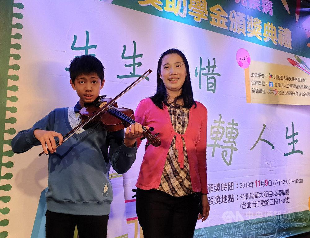 今年13歲的陳泓宇(左)罹患粒線體代謝異常,每天至少要睡12小時,是媽媽周曉君(右)的「無尾熊」男孩。周曉君9日受訪表示,陳泓宇自小學接觸到小提琴後,深深被琴聲吸引,開啟學習之路,對練習樂此不疲;且有音樂陪伴,也有助舒緩他的不適。中央社記者陳偉婷攝 108年11月9日