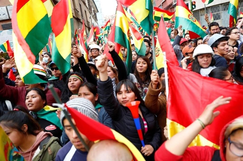 玻利維亞10月大選傳出爭議引爆民眾示威,總統莫拉萊斯11月10日宣布下台,引發民眾慶祝但盟國譴責的兩種反應。圖為9日玻國民眾高舉國旗走上首都拉巴斯街頭。(路透社提供)