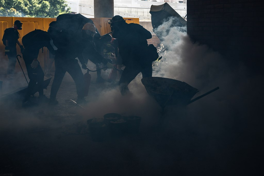 香港「反送中」示威者11日發起「三罷行動」,防暴警察進入香港中文大學和理工大學校園追捕黑衣示威者,並發射催淚彈。圖為理工大學學生在警方施放催淚彈後,使用滅火器撲滅。(法新社提供)
