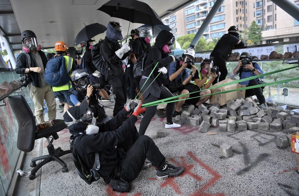 反送中示威者12日上午集結於香港歌和老街近城市大學學生宿舍一段,警方到場驅散時,在橋上的示威者以大型彈弓向警員發射石塊並丟擲汽油彈。(中通社提供)中央社 108年11月12日