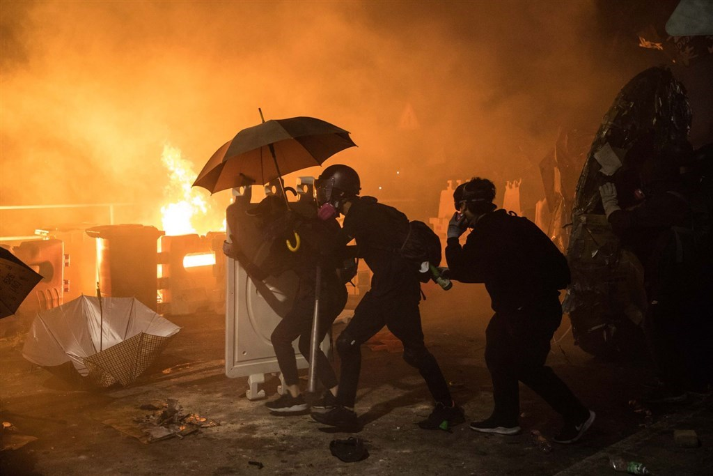 「反送中」示威者堵路及破壞鐵路等,導致香港交通幾近癱瘓,香港教育局宣布本地學校14日全部停課。圖為香港中文大學「反送中」學生12日在校園周邊與警方對峙,警方發射催淚彈,學生丟汽油彈反擊。(法新社提供)