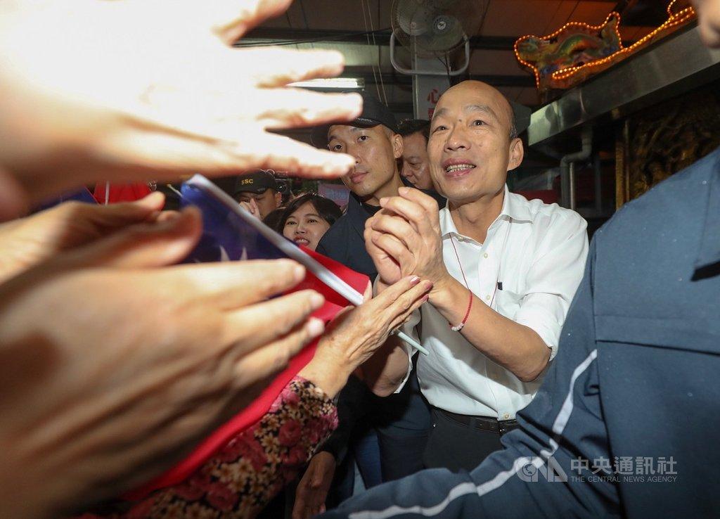國民黨總統參選人韓國瑜(右)18日晚間到台北內湖桂竹宮參香,與力拚連任的黨籍立委李彥秀同台造勢,受到支持者熱情歡迎。中央社記者裴禛攝 108年11月18日