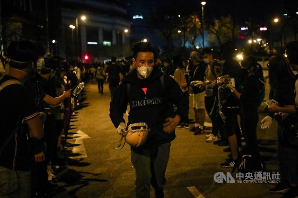 香港理工大學內的反送中示威者持續被港警包圍,校外的示威民眾18日深夜在尖東一帶與警方對峙,將頭盔從後方運往前線。中央社記者吳家昇攝 108年11月19日