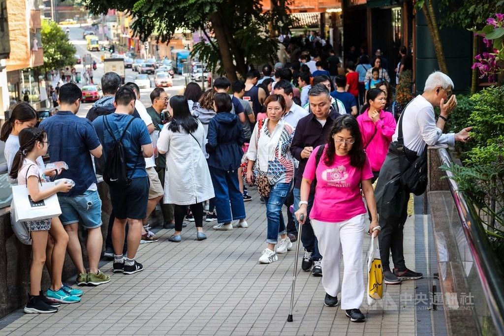 香港近日抗爭情勢逐漸趨緩,24日區議會選舉如期舉行,投票時間為24日上午7時30分至晚間10時30分。圖為灣仔郵政局延伸至天橋的排隊人龍,人潮多到看不到投票站。中央社記者吳家昇攝 108年11月24日