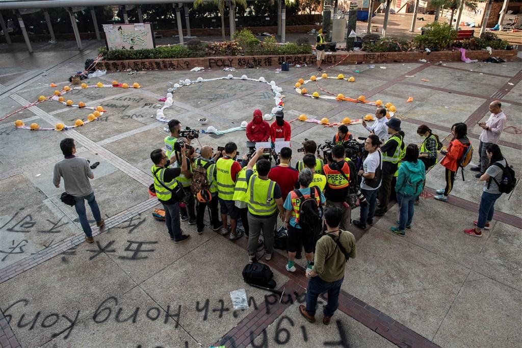 留守理大校園內的示威者24日推派代表(後排紅衣者)會見媒體,其中一名代表Ron(化名)表示,估計目前理大校園內還有約30名示威者。(法新社提供)