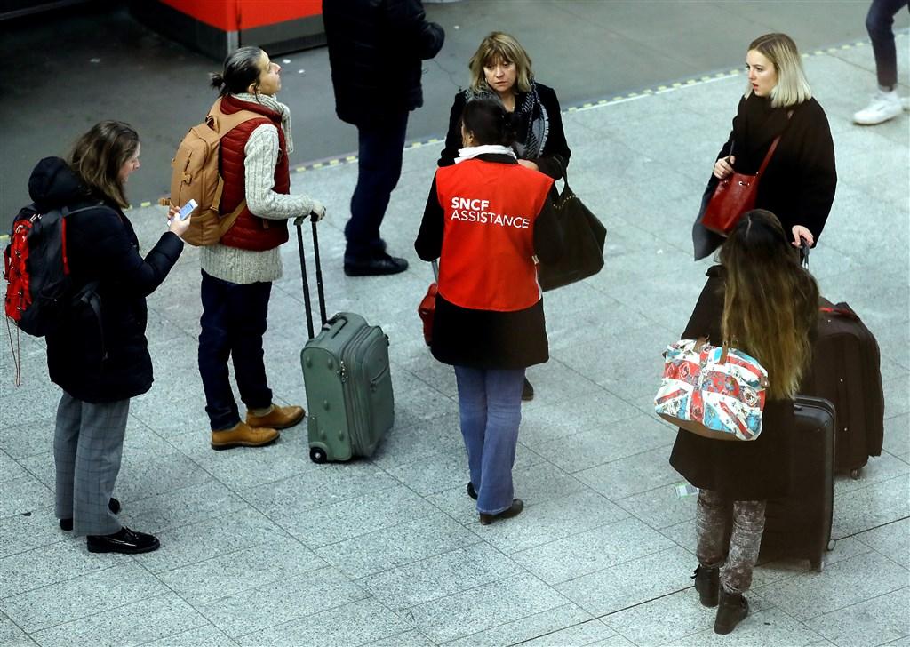 巴黎大眾運輸公司工會宣布5日起無限期罷工,抗議總統馬克宏改革退休制度,法國國家鐵路公司也說,全國90%高鐵列車5日將停駛。圖為鐵路公司人員4日協助旅客。(法新社提供)