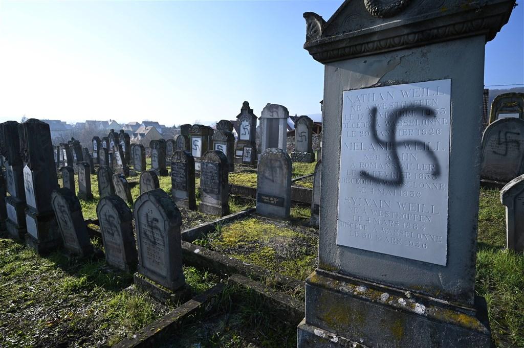 法國東部大城史特拉斯堡附近一個猶太墓園裡,107座墳墓遭人畫上納粹黨徽等塗鴉,內政部長視察後表示「這是可憎的反猶行為」。(法新社提供)