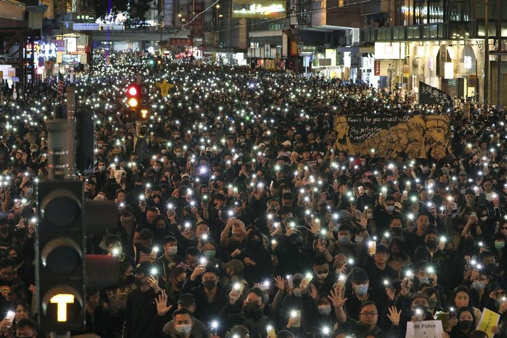 香港民陣8日晚間宣布,1208遊行共80萬人上街。活動下午3時準時從維多利亞公園出發,遊行隊伍入夜後亮起手機燈光。(共同社提供)