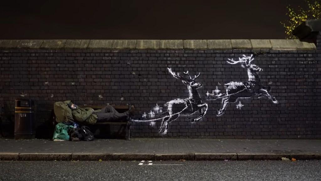 英國知名塗鴉藝術家班克西又有耶誕新作品,他在一張遊民棲身的長椅旁,畫上兩頭替耶誕老人駕車的馴鹿。( 圖取自banksyfilm YouTube頻道網頁youtube.com)