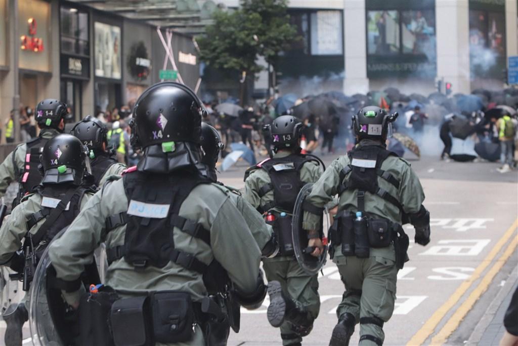 外媒報導,香港監警會就審視「反送中」風波所委聘的國際專家小組成員,認為監警會權力與調查能力嚴重不足,不能逼使警員提供證據,已全部辭職。圖為防暴警察發放催淚彈後追趕反送中示威者。(中央社檔案照片)