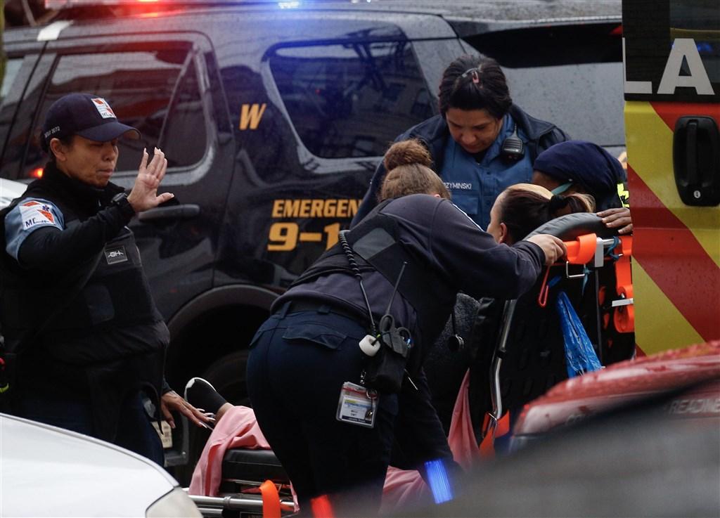 美國新澤西州澤西市一家雜貨超商10日下午驚傳槍擊案,至少6人喪生。圖為槍擊案現場一名婦女接受醫療救助。(法新社提供)