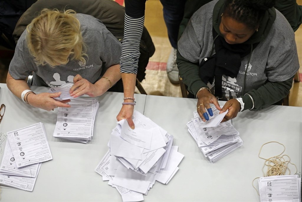 英國5年內舉行第3次大選,12日晚間10時結束投票,根據選後出口民調,保守黨將大獲全勝。圖為選務人員整理選票。(法新社提供)