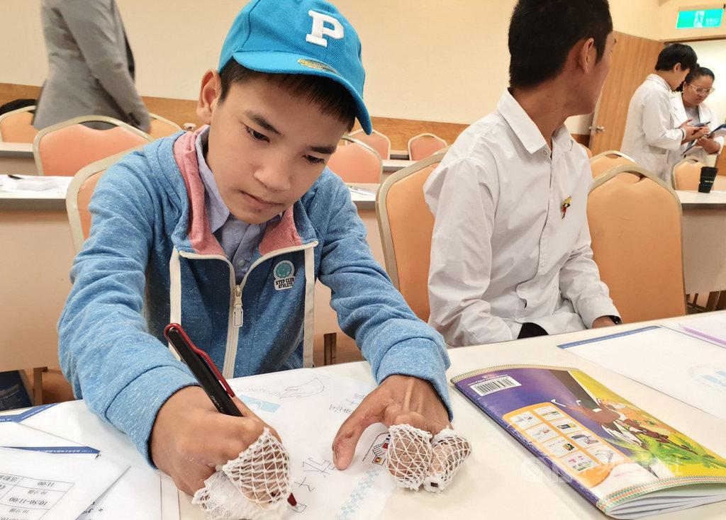 緬甸男孩張子墨(左)患有先天性手掌五指骨並連的疾病,在台灣完成2階段的手指分割手術,雙手已有基本抓握功能,經復健後已能單手寫下自己的名字。中央社記者陳偉婷攝 108年12月23日