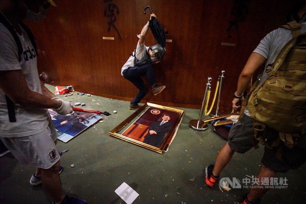 香港政府3月31日提出逃犯條例修訂草案,6月9日爆發反送中運動,反對逃犯條例修訂的民眾發起抗爭。圖為示威者7月1日衝進立法會會議廳,拆下並腳踹歷任立法會議員的肖像照。(中央社檔案照片)