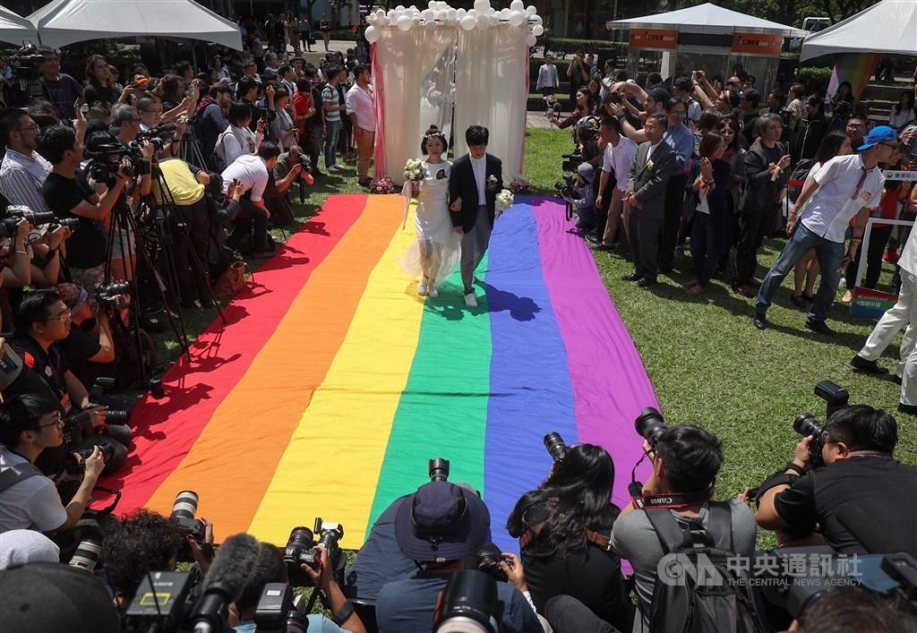 森路透基金會26日列出2019年LGBT+全球10大新聞,其中台灣同婚合法化也榜上有名。圖為5月24日同婚登記開跑,同志新人以彩虹旗當作紅毯步入會場。(中央社檔案照片)