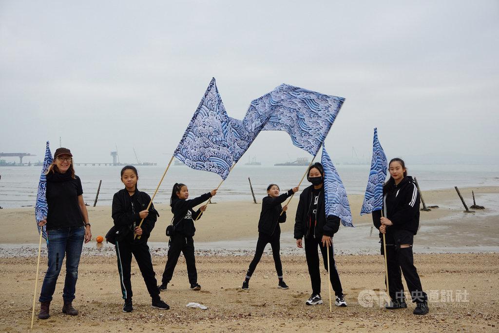 在金門縣文化局協助下,澳洲藝術家肯恩(Penelope Cain)(左)5日在金門慈堤海灘創作,並與金門流行舞蹈團的孩子們合影。中央社記者黃慧敏攝 109年1月5日