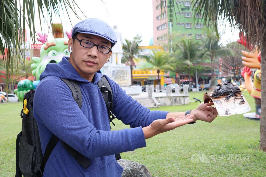來自中國湖南、現居花蓮的39歲青年周曙光,8日在花蓮火車站廣場以燒掉中國護照方式,鼓勵大家珍惜台灣民主和自由,踴躍投票。中央社記者李先鳳攝 109年1月8日