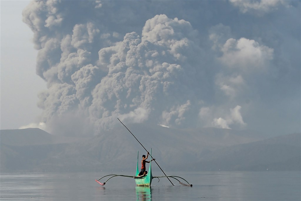 菲律賓塔爾火山13日突然噴發火山灰和蒸汽,馬尼拉國際機場已關閉,數百航班停飛,估計恐有45萬人須撤離。(法新社提供)