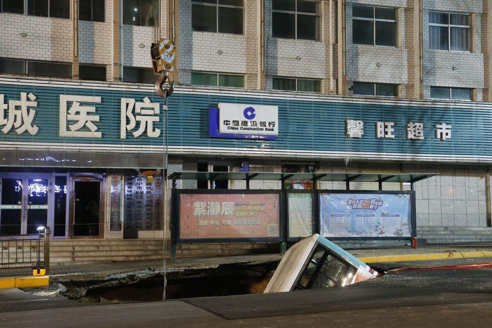 中國青海省西寧市一處公車站13日下午忽然發生路面塌陷,導致一輛正在進站的公車車頭朝下墜入坑中。(中新社提供)