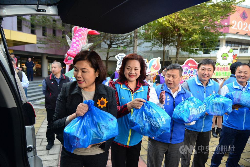 農曆春節將至,雲林縣長張麗善(前左)與縣議員、縣府主管及志工人員,15日將送給弱勢民眾的緊急及保暖物資裝袋,以接力的方式,送上轉運車。中央社記者蔡智明攝 109年1月15日