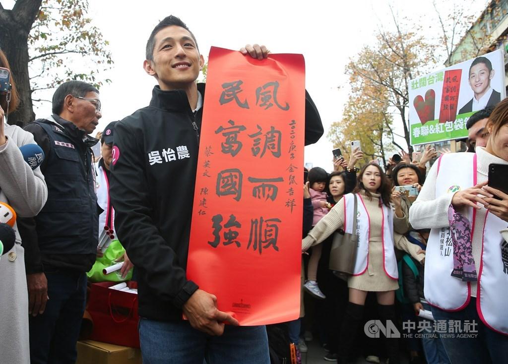 參選立委失利的民進黨候選人吳怡農(前)18日在台北市錦西街和民生西路70巷口發送春聯和紅包袋,向民眾拜早年。中央社記者謝佳璋攝 109年1月18日